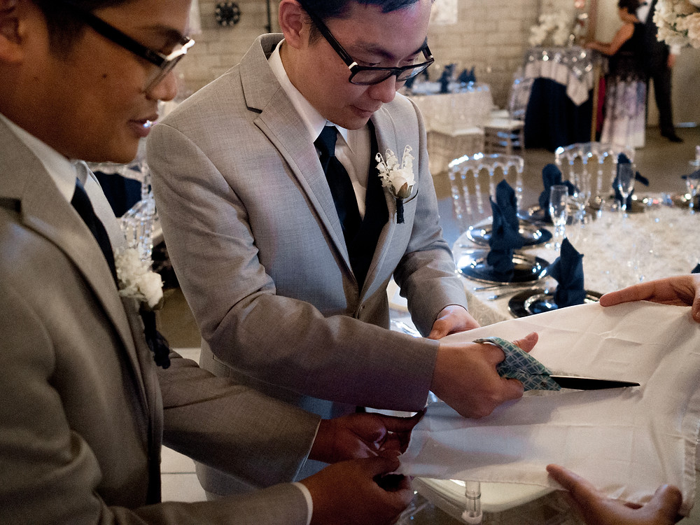 Groomsmen cutting a pocket square in two to replace one that was lost