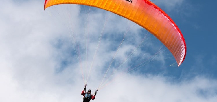Person paragliding using an orange glider