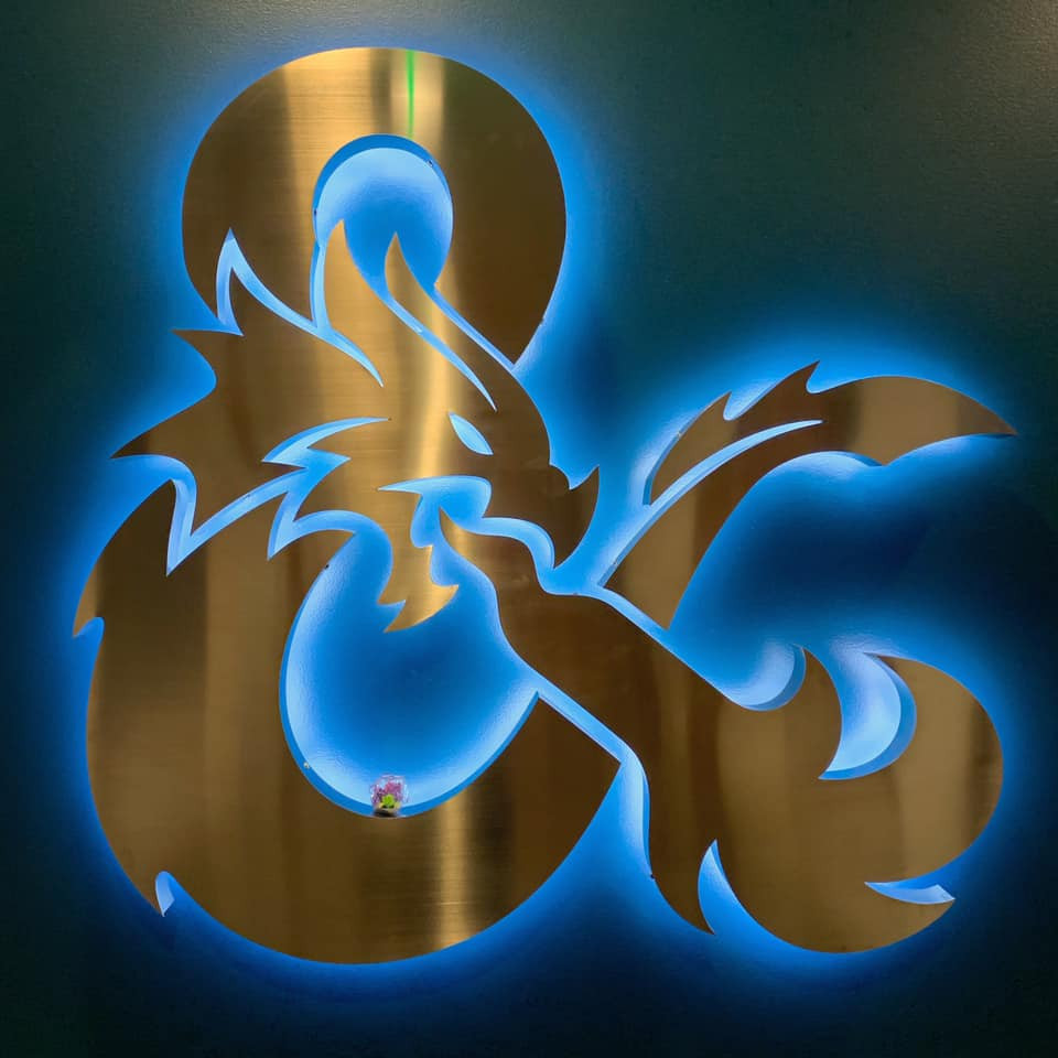 Silver metal D&D logo ampersand backlit with blue light. DOTS dragon d20 sitting inside bottom curve.