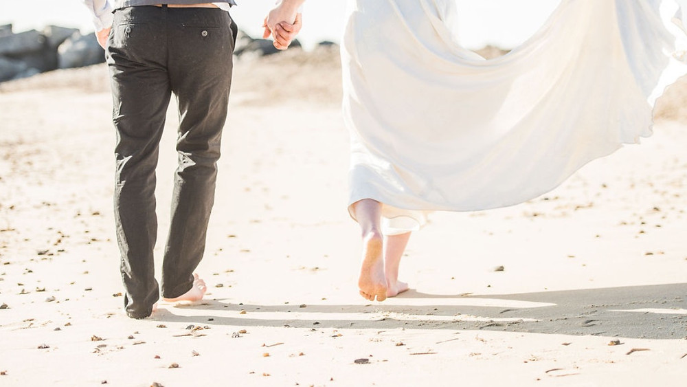 Barefoot bride and groom walk hand in hand on Essex beach