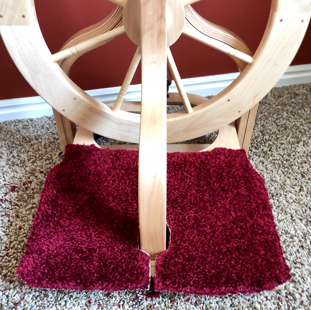 A castle-style double treadle spinning wheel with red, textured treadle covers.