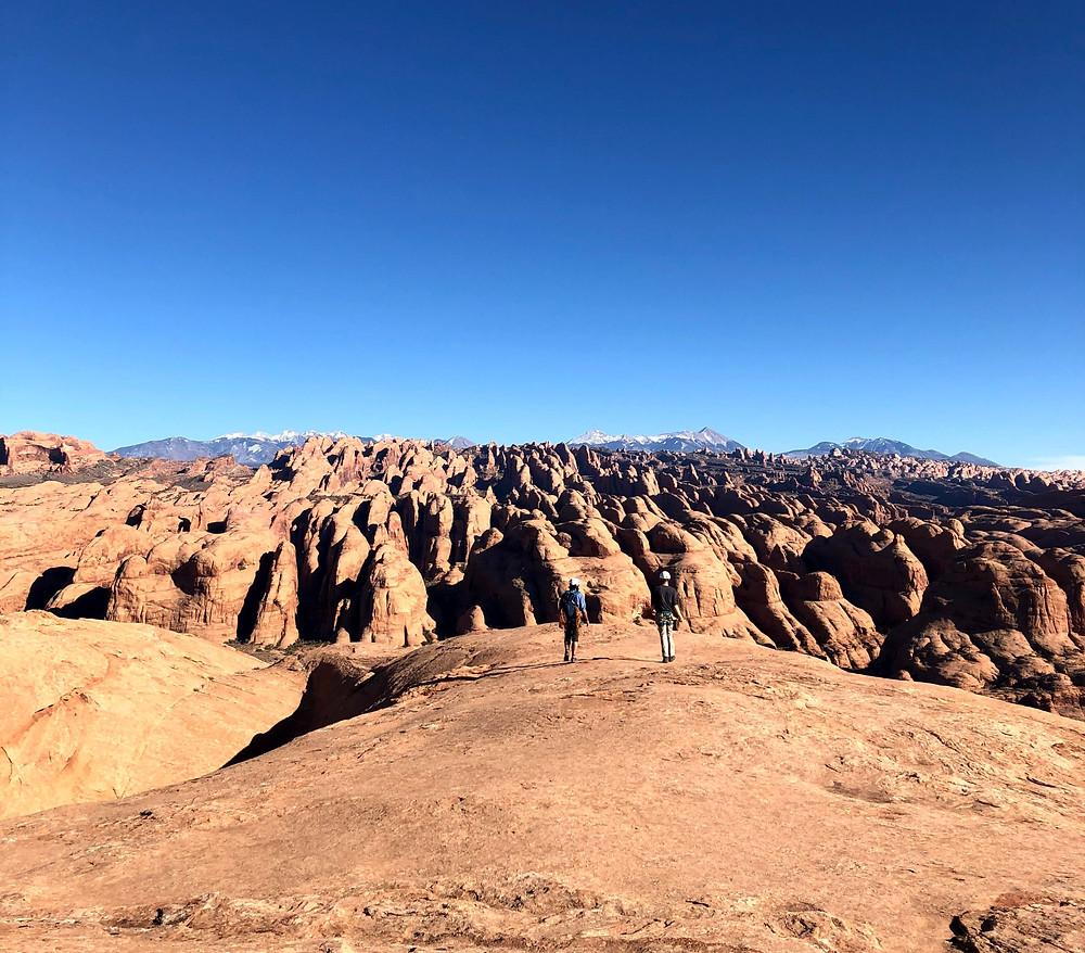 Two people walking on sandstone ridge in Utah.