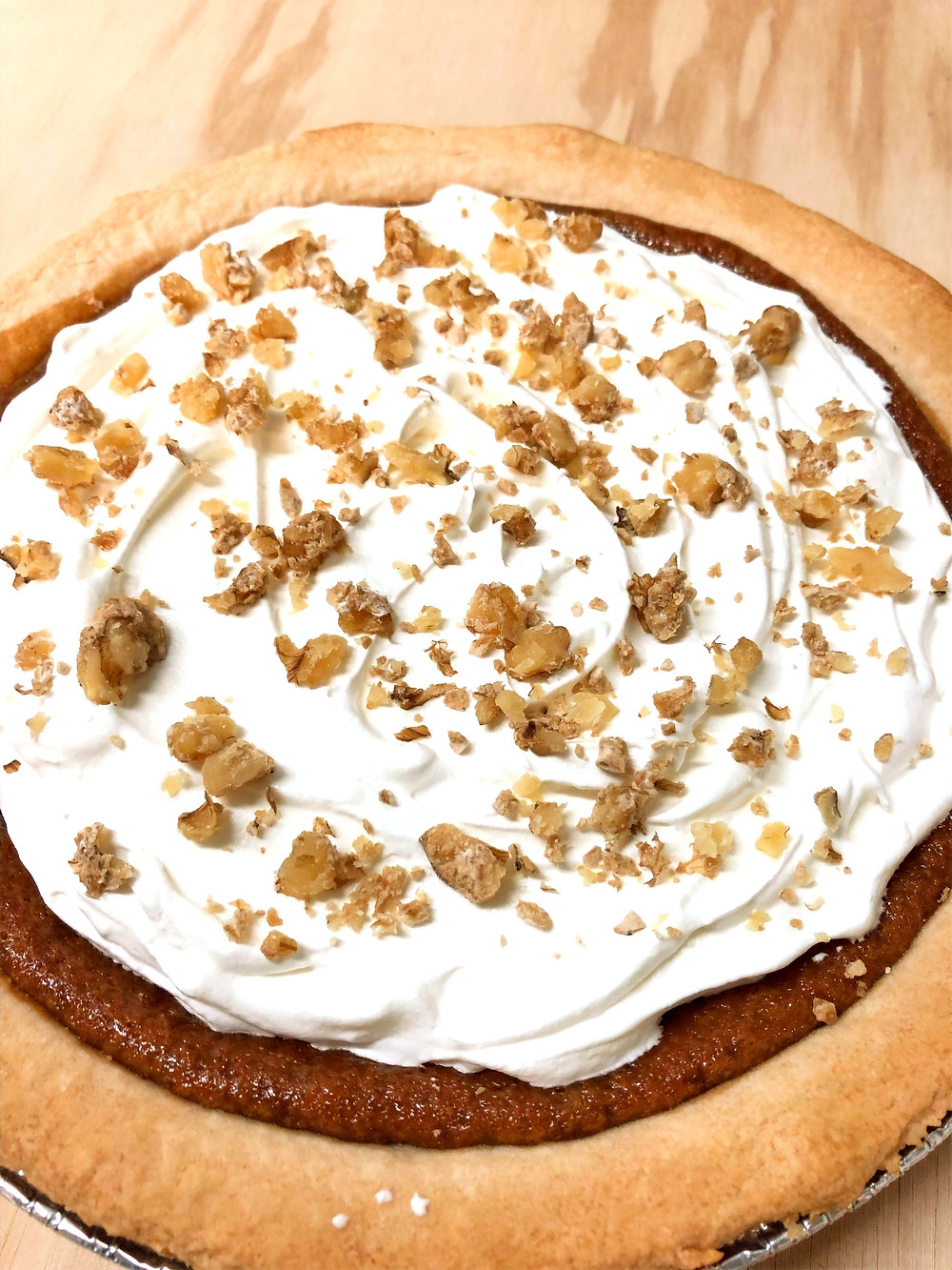 A pie with whipped cream and nut topping sits on a wood table.