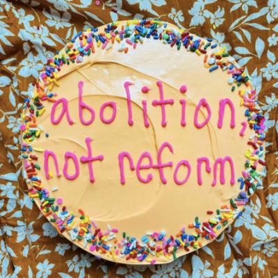 "A cake with ""abolition not reform"" written in pink icing"