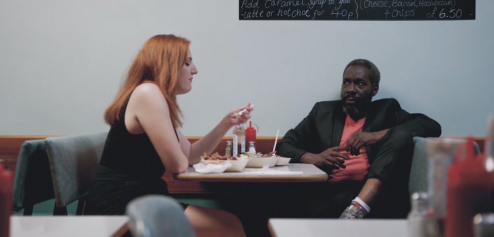 Still of Ben (Gary Beadle) and Margaret (Jessica Chamberlain) sitting in a diner in the film 'Squall'
