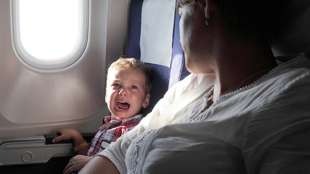 Niño llorando en el avión.