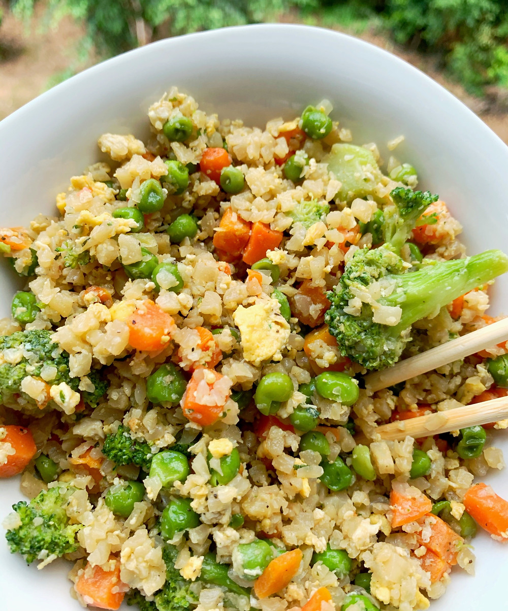 overhead shot of cauliflower fried rice with chopsticks sticking out of the bowl
