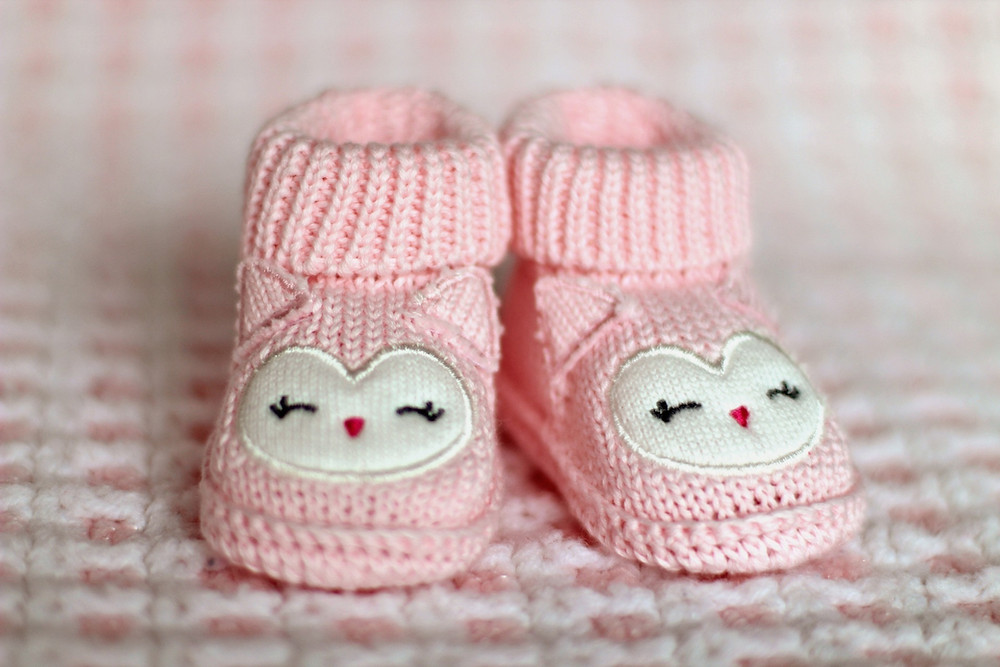Pink knit baby booties decorated with cheerful kitten faces and tiny ears.