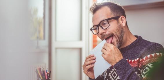 Man licking envelope