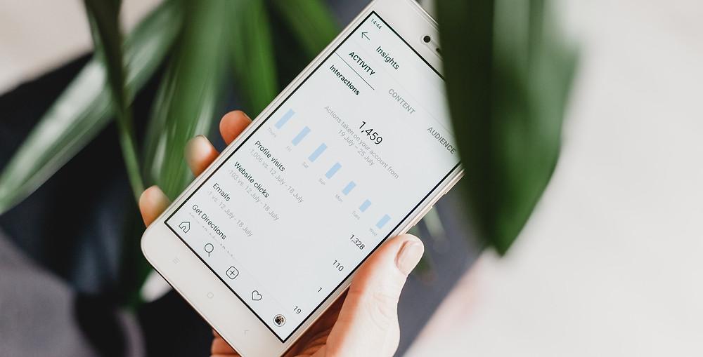 Smartphone in der Hand, zeigt Screen von Instagram Insights
