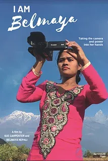 A young Nepali woman in a pink dress looks through the viewfinder of a video camera with the Himalayas in the background.