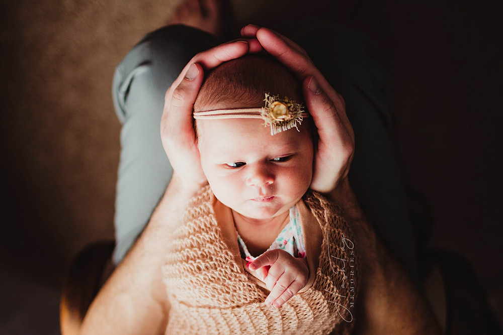newborn baby girl in headband, dad hands, indianapolis newborn photographer