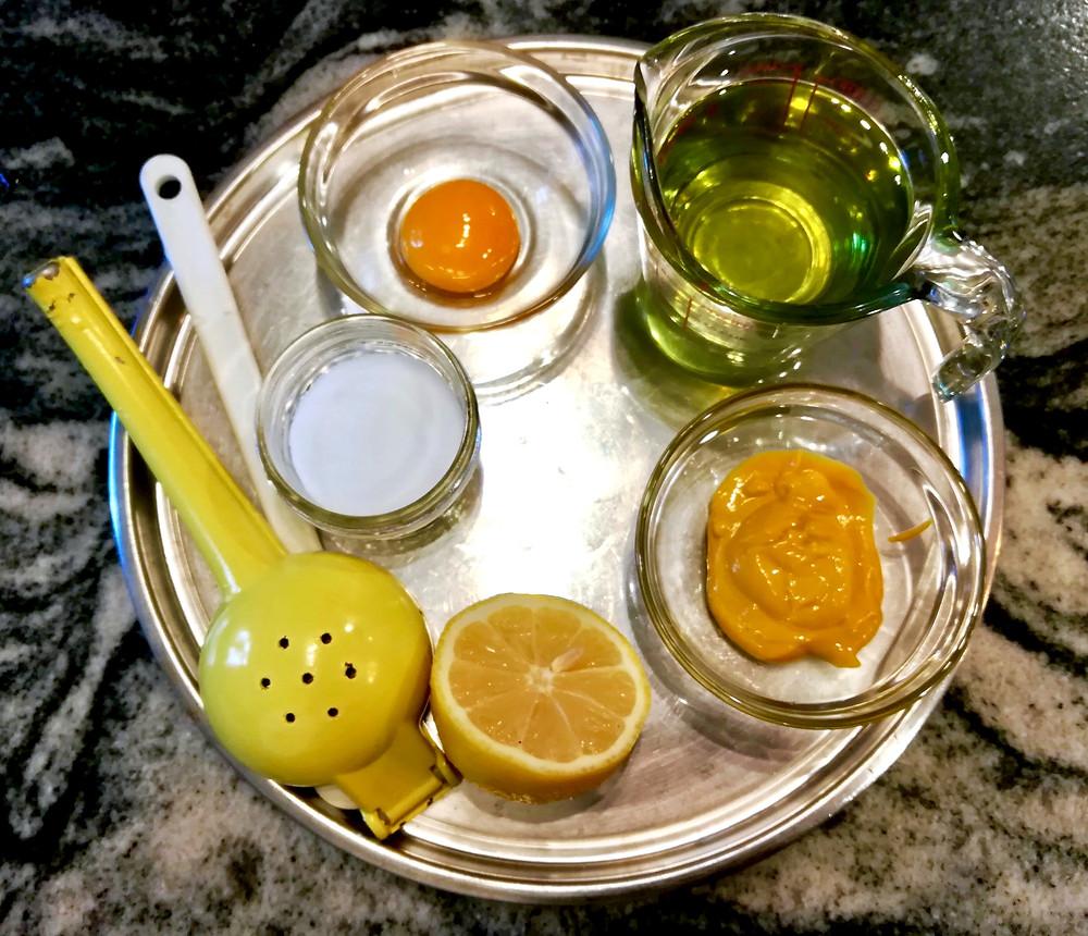 Tray with mayonnaise ingredients: egg yolk, oil, mustard, lemon, and salt
