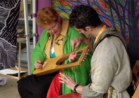 Chip teaching someone how to play the lyre