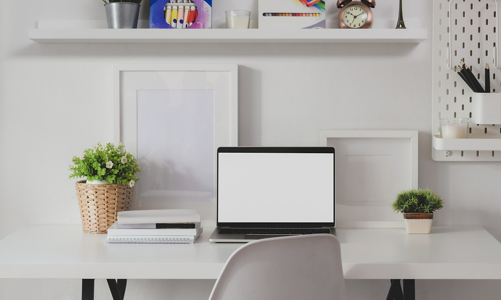A computer on a white desk in a tidy office with plants.