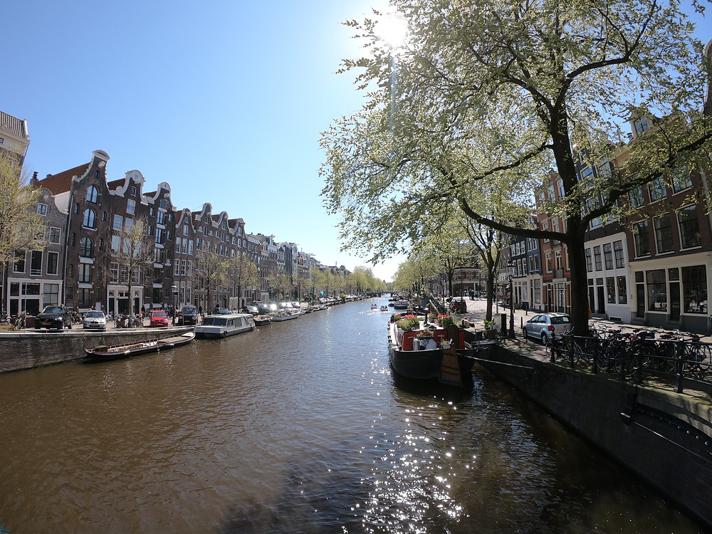 Foto de um canal típico de Amsterdam, com casas barco atracadas nas margens e construções tradicionais nas margens.