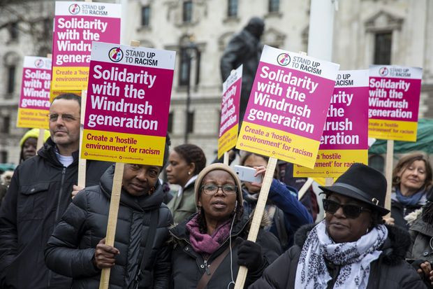 People holding banners of protest at the Windrush scandal