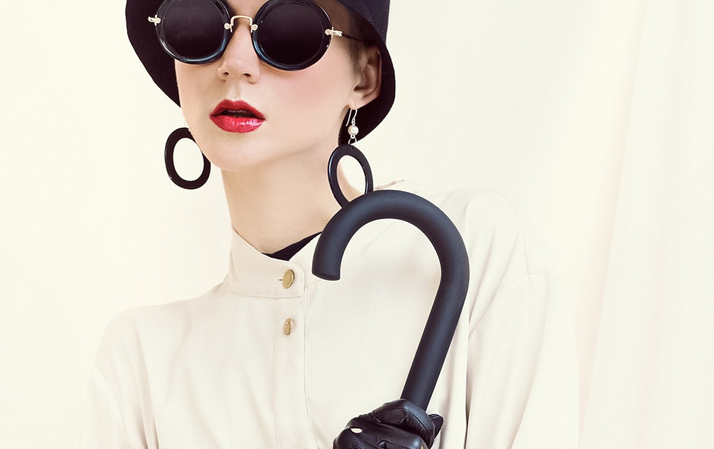 Model wearing cream coat sunglasses hat and holding an umbrella