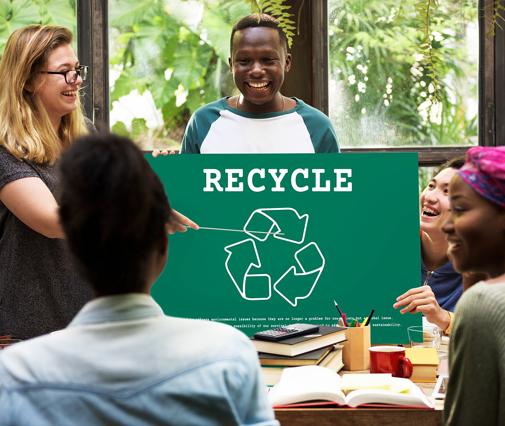 Male holding Recycle sign and smiling