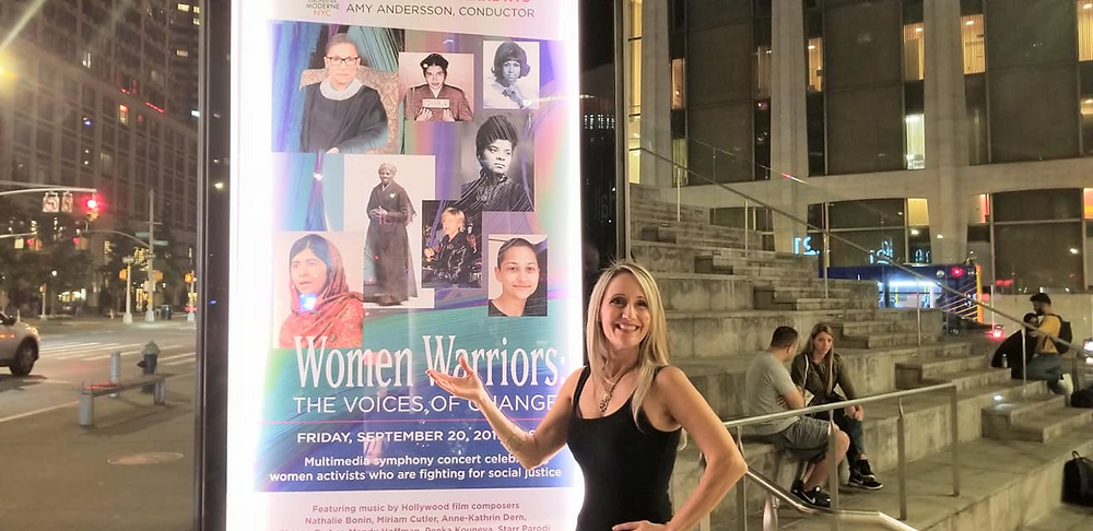 "Sharon standing next to the Lincoln Center concert poster ""Women Warriors"""