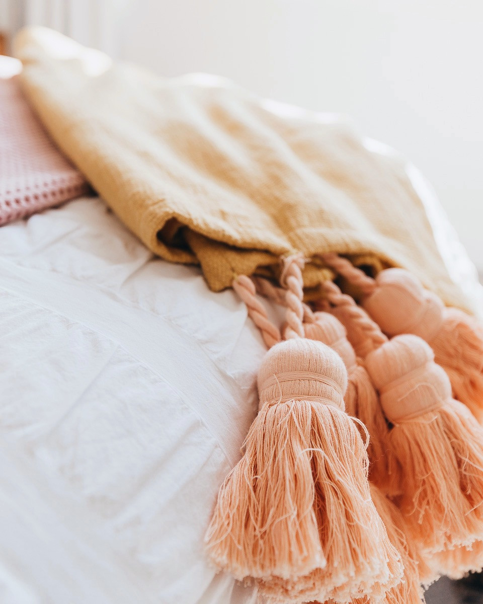 A blanket with large tassels laying on the end of the bed.