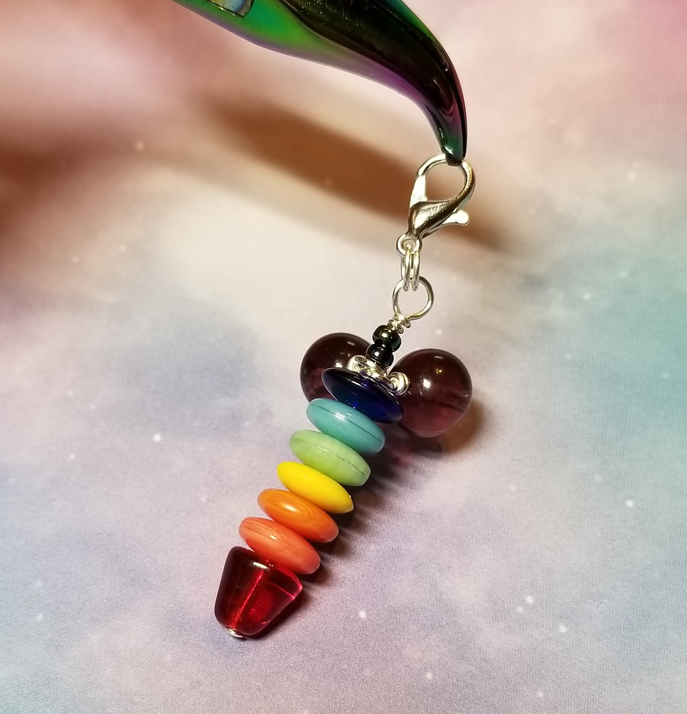 Rainbow Penis Zipper Charm being held by chroma bent nose pliers