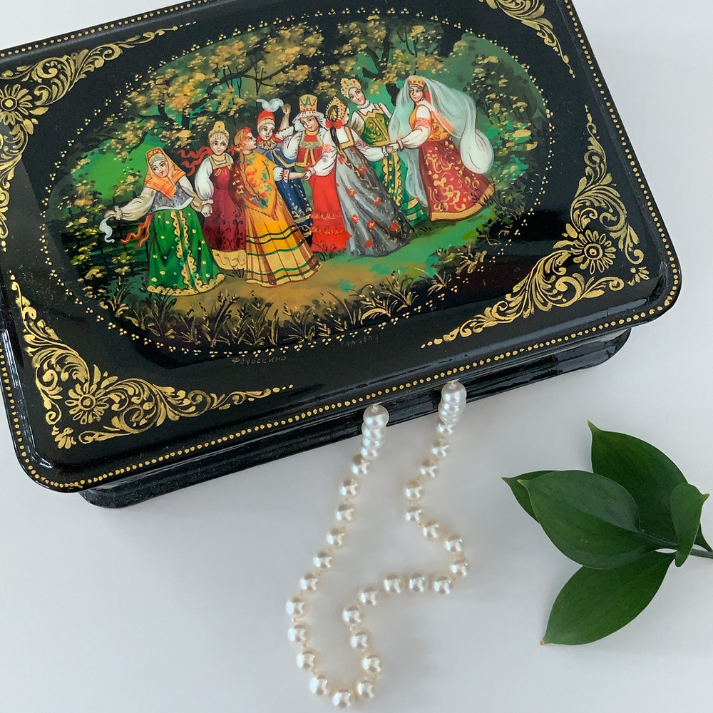 Strand of freshwater pearls hanging from a colourful Russian jewellery box