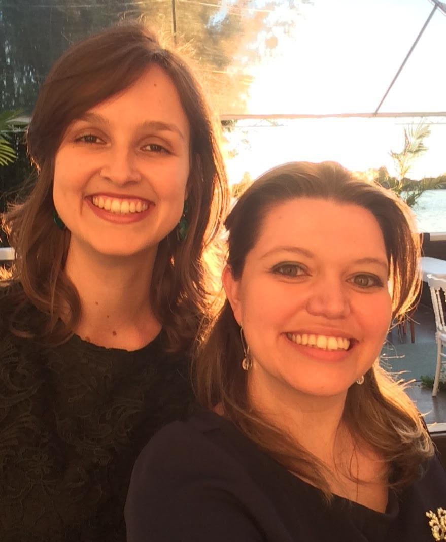 Cofundadoras da Palavra Bordada, Denise Waskow à esquerda da imagem, e Carolina Rocha à direita, posam para foto em um ambiente ao ar livre, iluminado pelo sol.