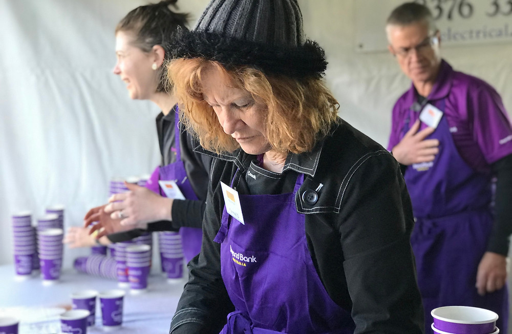 Beyond Bank Staff serve coffee at a volunteering event wearing their signature purple colour.