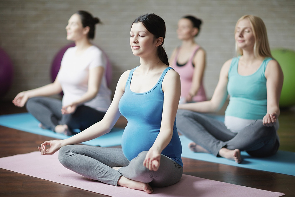 A group of pregnant woman are sitting in meditative poses on exercise mats.