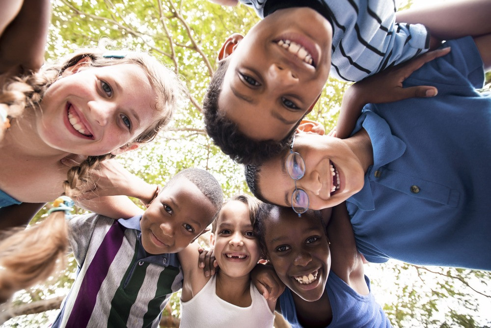 A group of smiling children link arms in a circle. Their faces peer down at the camera.