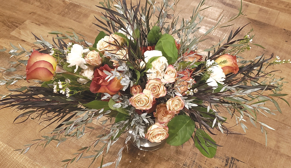 Flower arrangement with roses, wax flower and eucalyptus.