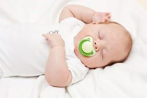 Bebé durmiendo con un chupo en la boca