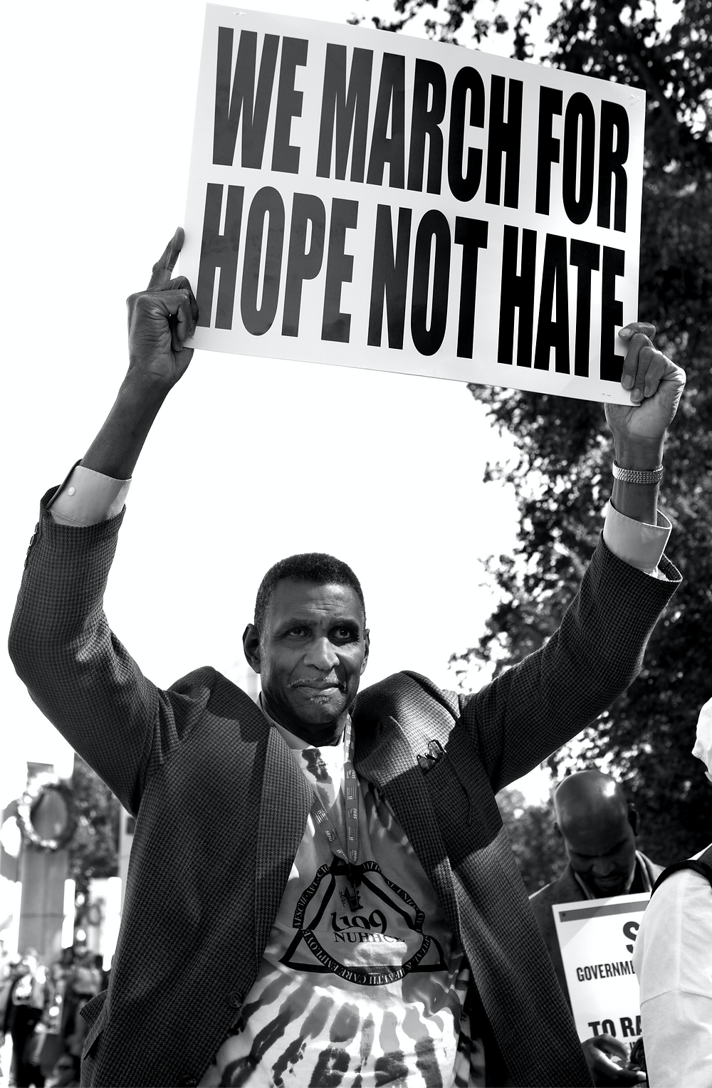 Black man holds up a sign that says, We march for hope not hate