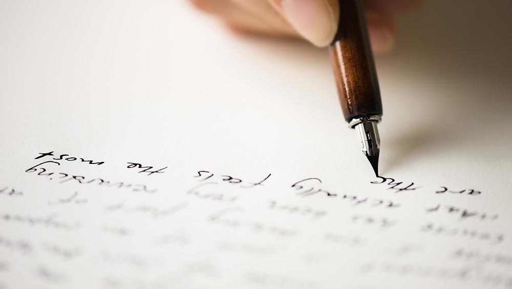Mano escribiendo carta.