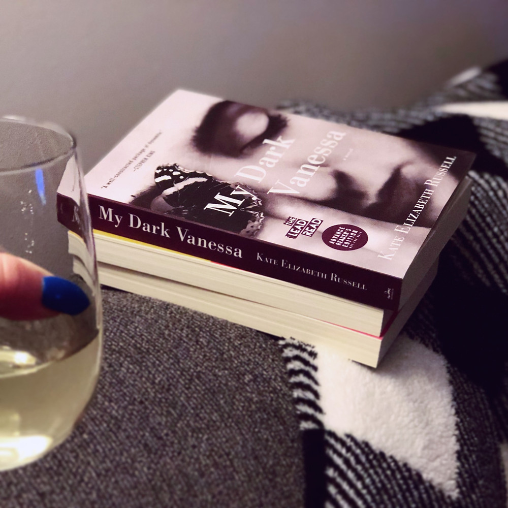 A wineglass and a stack of books with My Dark Vanessa on the top