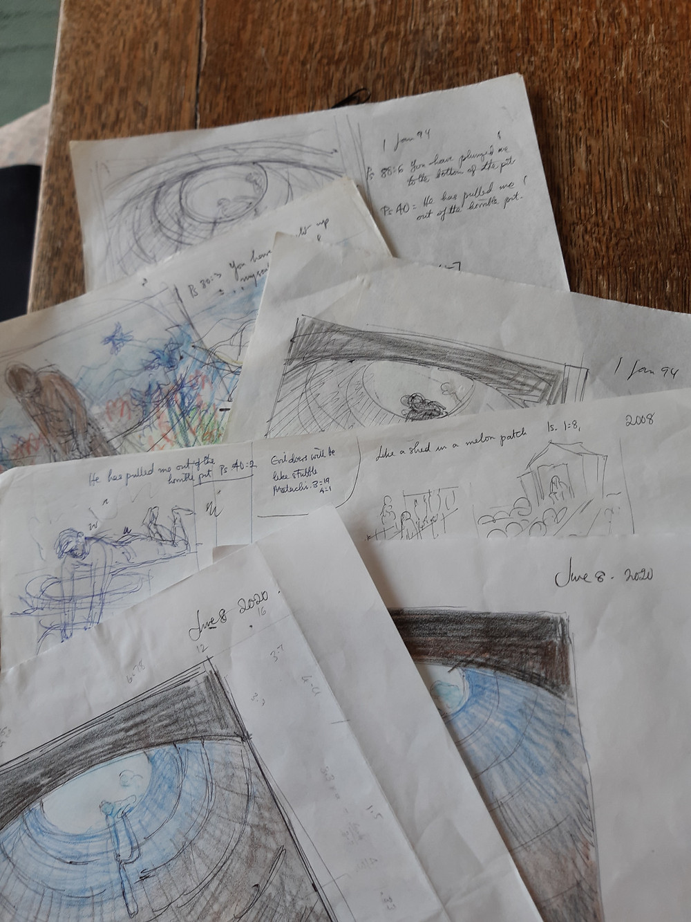 A pile of peter's sketches, no real details are obvious but some are in colour or in black and white using biro