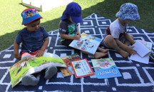 Children reading and learning outdoors at our Otahuhu childcare center - Eduplay Otahuhu