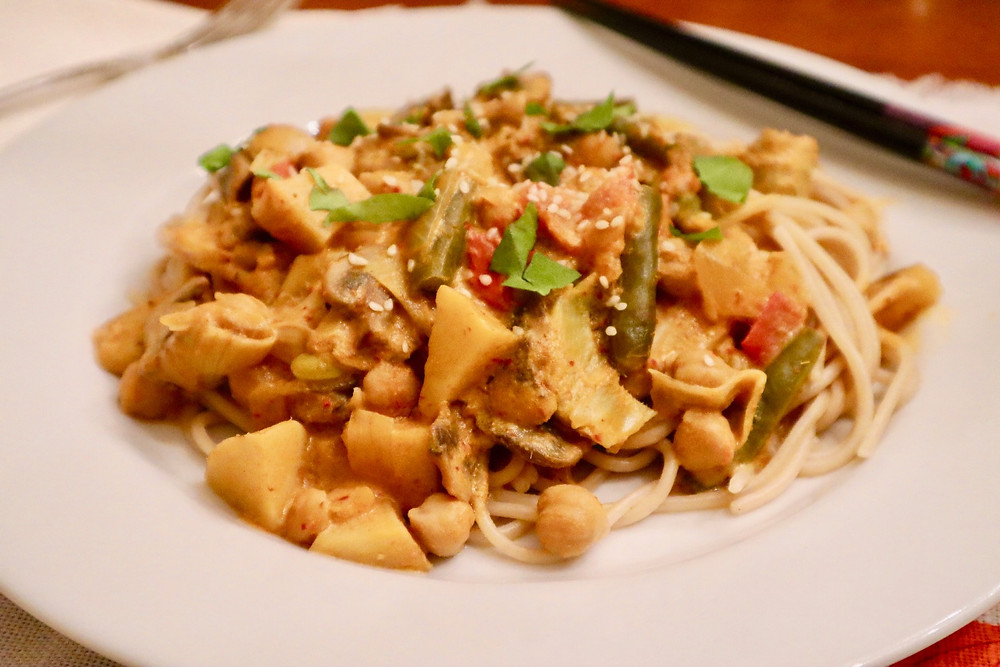 A vegan, whole food, plant-based Thai pasta that uses a red curry sauce with assorted vegetables over spaghetti noodles.