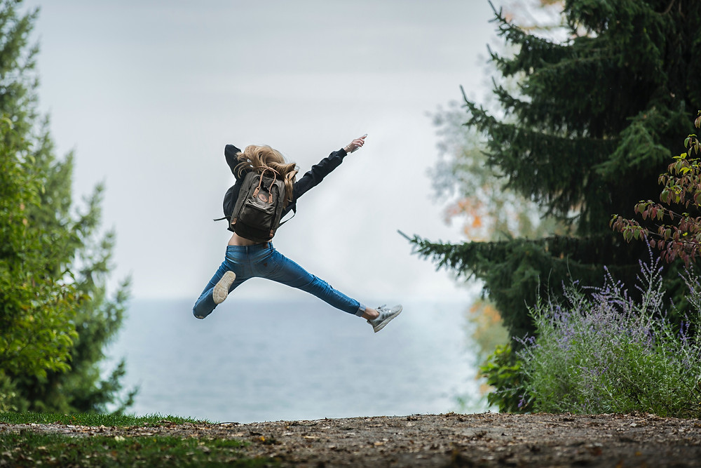 Photo of a woman jumping while on a hike