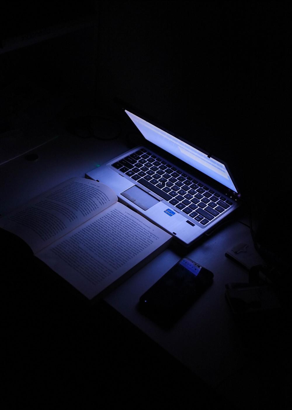 לפטופ של חברת אייץ' פי מדגם פבילון על שולחן עבודה חשוך עם ספר וטלפון נייד