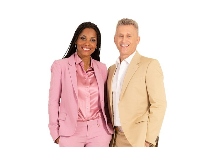 Black woman dressed in pink pant suit and matching shirt stands to the right of her husband who is dressed in khaki suit and white shirt.