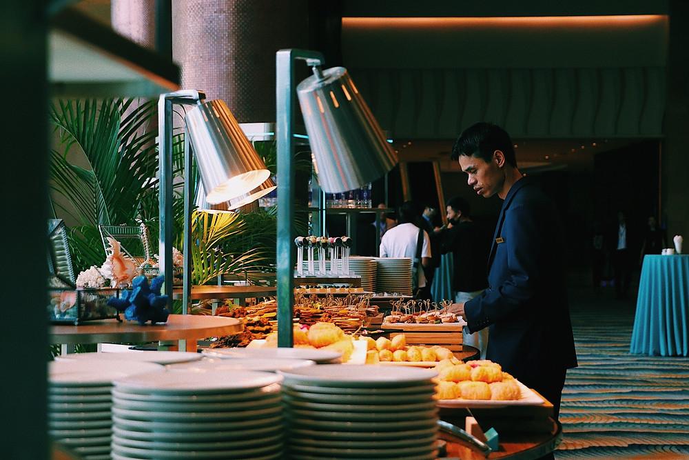 A man looking at a buffet of food.
