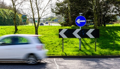 white car exiting a roundabout