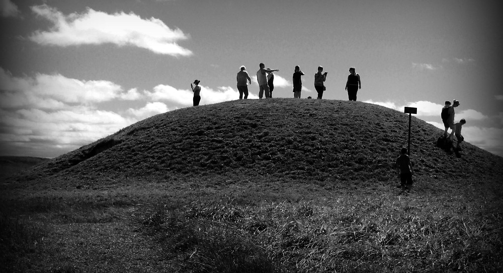 Black and white image of the Mound of Hostages at Tara with silhouettes of 9 people standing on top.