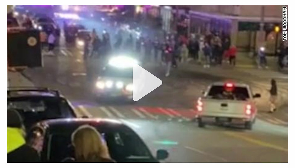 Police officer driving through crowd, injuring at least one person.