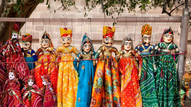 Colorful and dressed puppets hung on a stick