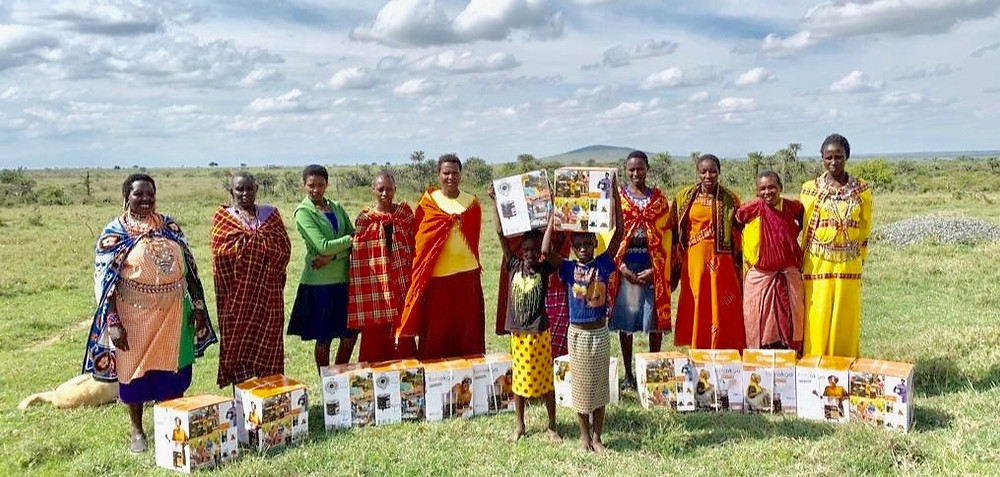 Ladies showing off their jikos with a stack of wood behind them that will last many months when using jikos as opposed to weeks when building a traditional wood fire.