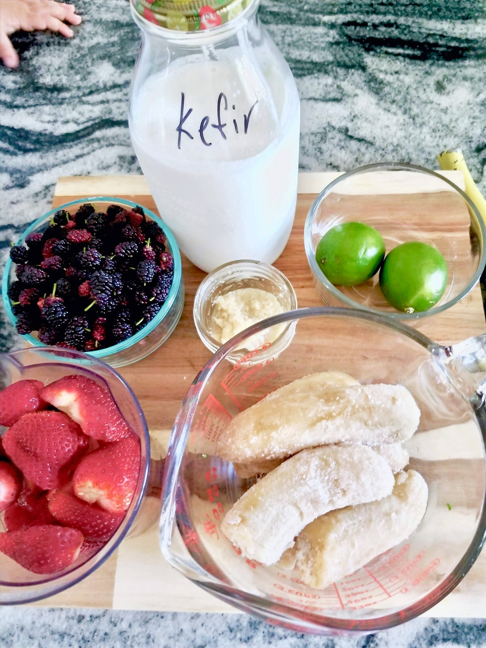Ingredients to make a mulberry smoothie: mulberries, strawberries, bananas, lime, kefir, and ginger puree