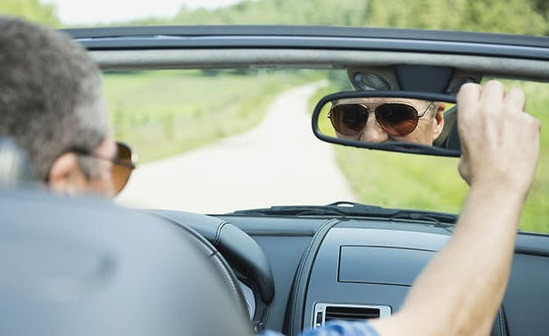 Man with sunglasses behind the wheel of a car